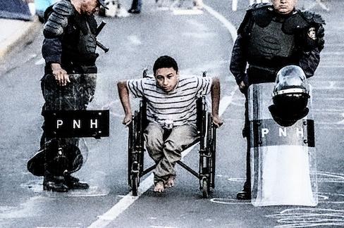 Hondurasilainen ihmisoikeusaktivisti Erlin Mejia kulkee pyörätuolissa kahden mellakkavarusteisen poliisin välistä.