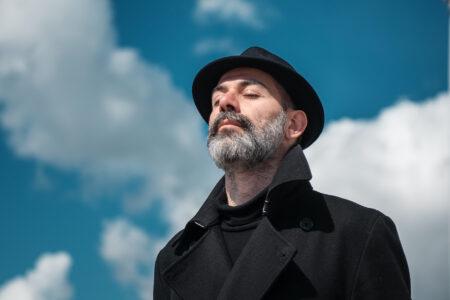 Pilapiirtäjä Kianoush Ramezani seisoo ulkona silmä kiinni taustallaan sininen taivas, jolla on muutamia vaaleita pilviä