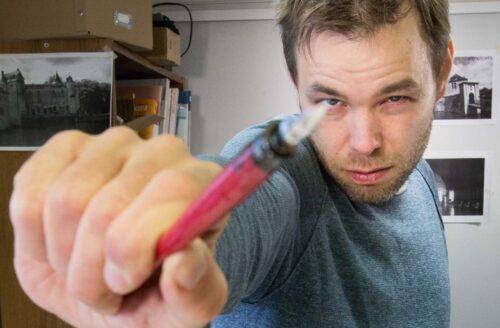 Ville Ranta pitää kynää kohti kameraa ojennetussa kädessään.