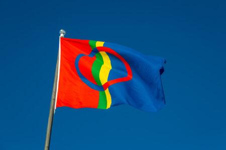 Saamen lippu lipputangossa kuvattuna sinistä taivasta vasten.