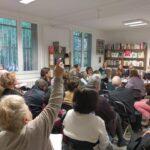 Keskustelelua rauhankomiteoiden kokouksessa Pariisissa. Salissa paljon osallistujia, taustalla johtokunta pöydän ääressä.