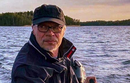 Kirjailija Juha Ruusuvuori ajaa perämoottoriveneellä merellisessä maisemassa
